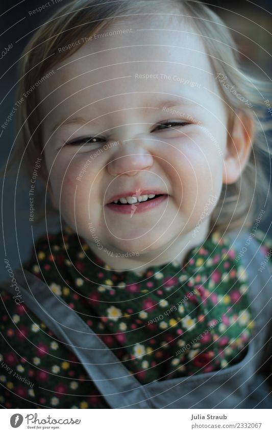 Kleinkind Mädchen freches Grinsen feminin Kindheit 1 Mensch 1-3 Jahre Bluse Latzhose blond Lächeln frei Fröhlichkeit lustig grau grün Freude Zähne zeigen