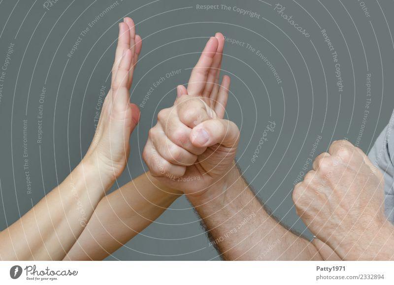 Frau hat abwehrend beide Hände gegen eine Mann erhoben der sie mit geballten Fäusten bedroht. Detailaufnahme der Hände. Mensch maskulin feminin Erwachsene Arme