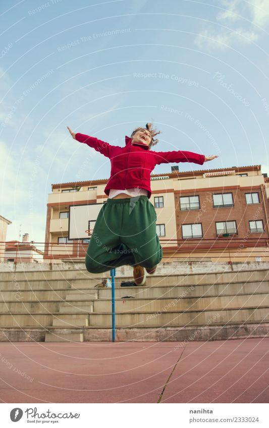 Junge glückliche Frau, die auf der Straße springt. Lifestyle Stil Freude Gesundheit sportlich Fitness Wellness Leben Sport Sport-Training Leichtathletik Mensch