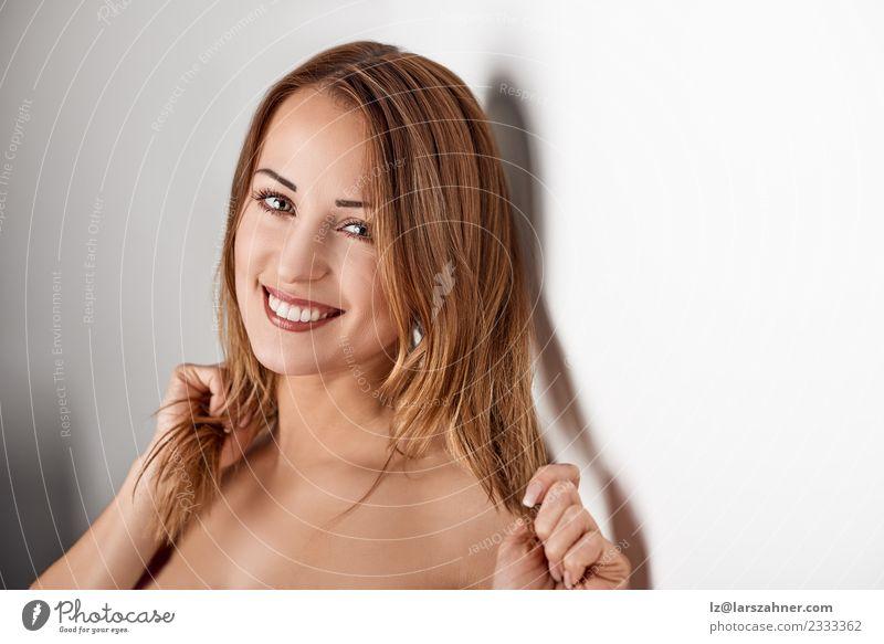 Junge lächelnde blonde Frau, die sich gegen eine Wand lehnt. Lifestyle schön Gesicht Behandlung Erwachsene 18-30 Jahre Jugendliche glänzend Lächeln Fröhlichkeit