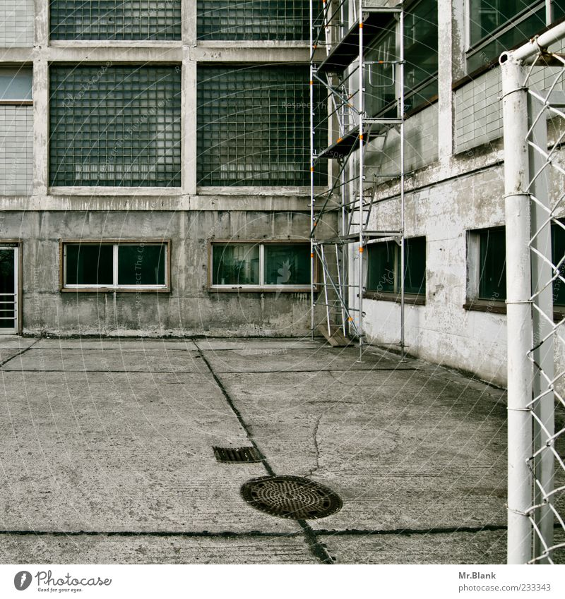betonter beton alt Einsamkeit Fenster Fassade kaputt trist verfallen Zaun Konstruktion Unbewohnt Lager verwittert Demontage vergessen Sanieren Gully