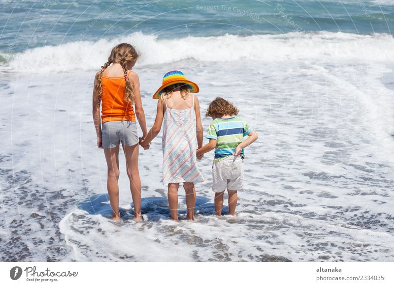 Drei glückliche Kinder spielen am Strand zur Tageszeit. Konzept der Sommerferien. Lifestyle Freude Glück schön Freizeit & Hobby Spielen Ferien & Urlaub & Reisen