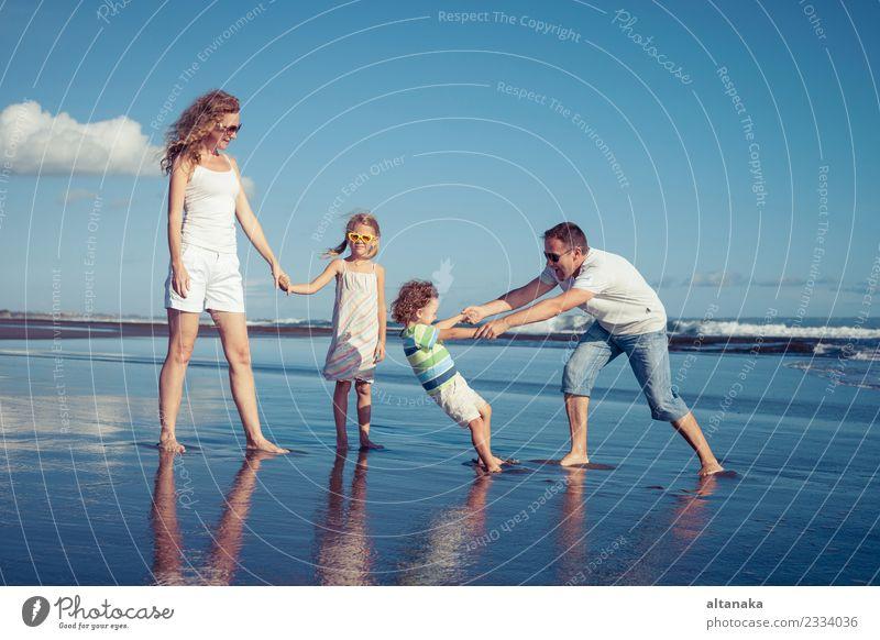 Glückliche Familie, die tagsüber am Strand spazieren geht. Lifestyle Freude Leben Freizeit & Hobby Spielen Ferien & Urlaub & Reisen Ausflug Freiheit Sommer