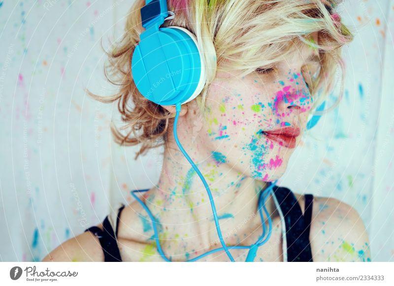 Junge Frau mit Farbe im Gesicht hört Musik. Lifestyle Stil Design exotisch Erholung ruhig Freizeit & Hobby Technik & Technologie Unterhaltungselektronik Mensch