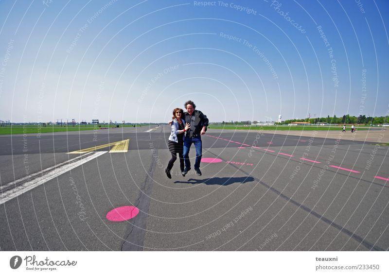 Taking Off Mensch Frau Mann Erwachsene Ferne Liebe springen Glück Paar Zusammensein Schilder & Markierungen Fröhlichkeit Luftverkehr Asphalt Vertrauen Fitness