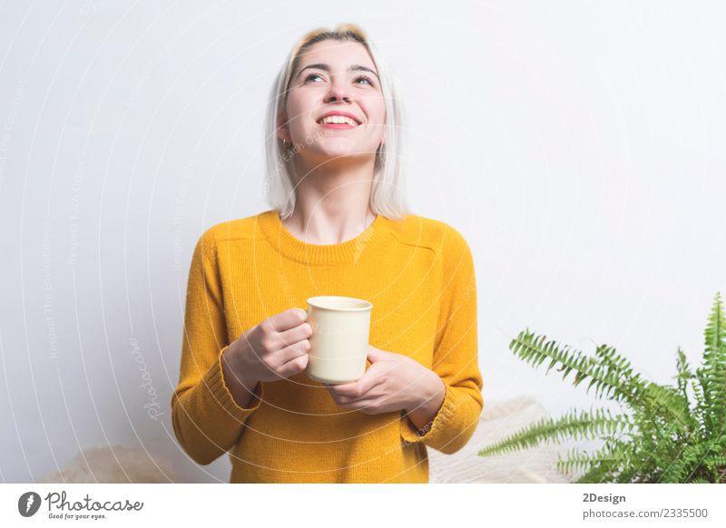 Fröhliche junge Frau hält eine Tasse Tee oder Kaffee. Frühstück Getränk trinken Heißgetränk Espresso Lifestyle Stil Glück schön Gesicht Gesundheitswesen