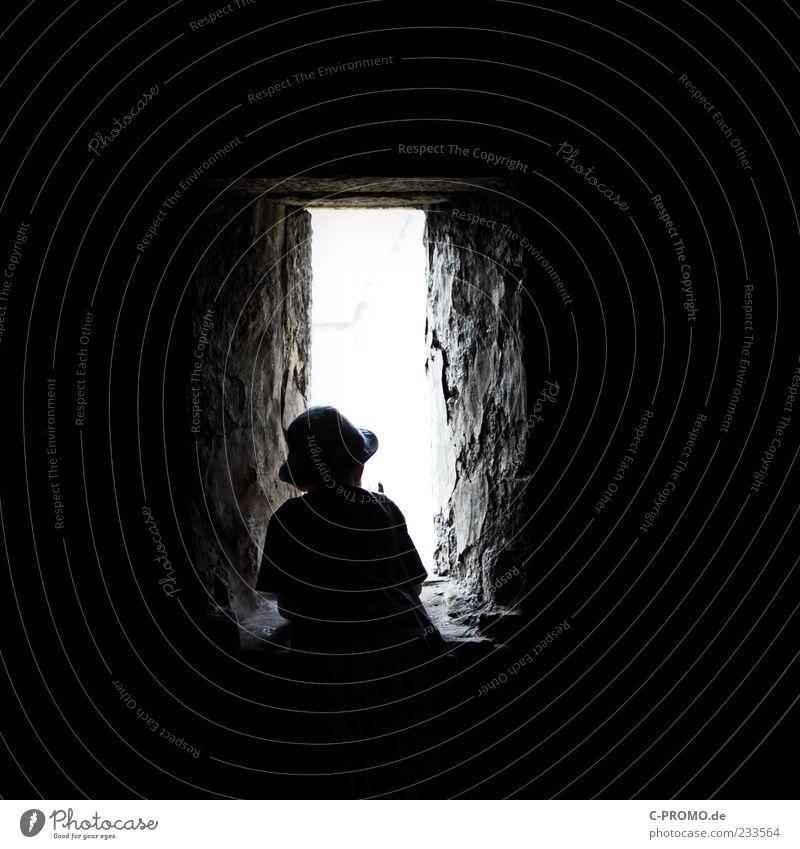 Lichtblick Mensch Kind schwarz dunkel Fenster Wand Junge Mauer Kindheit maskulin stehen Neugier Aussicht Hut Burg oder Schloss Denkmal