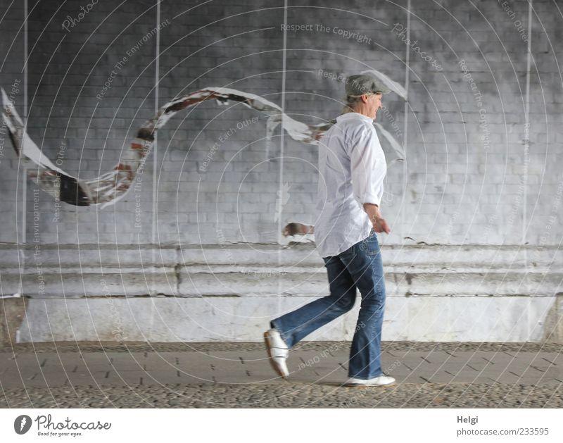 Frau mit Cap in Jeanshose und weißem Hemd läuft an einer Wand entlang Mensch Erwachsene Weiblicher Senior Leben 1 45-60 Jahre Tunnel Mauer Verkehrswege