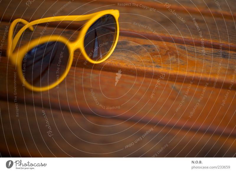 Sommersonnenbrille Lifestyle Tisch Holztisch Sonnenbrille braun gelb Gelassenheit Sommerurlaub sommerlich Farbfoto Außenaufnahme Menschenleer
