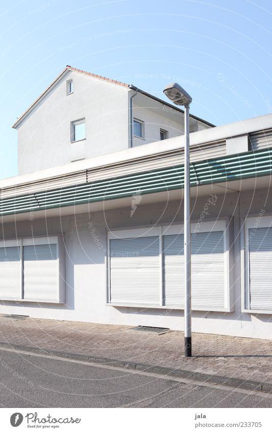 ladenzone Wolkenloser Himmel Haus Bauwerk Gebäude Architektur Ladengeschäft Ladenfront Mauer Wand Fassade Fenster Rollladen Laterne Straße Wege & Pfade