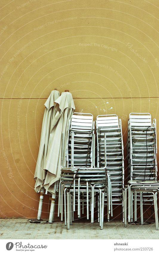 Hochstapler Möbel Stuhl Tisch Gartenstuhl Sonnenschirm Bar Cocktailbar Strandbar Mauer Wand Fassade trist Stapel schlechtes Wetter geschlossen Winterpause