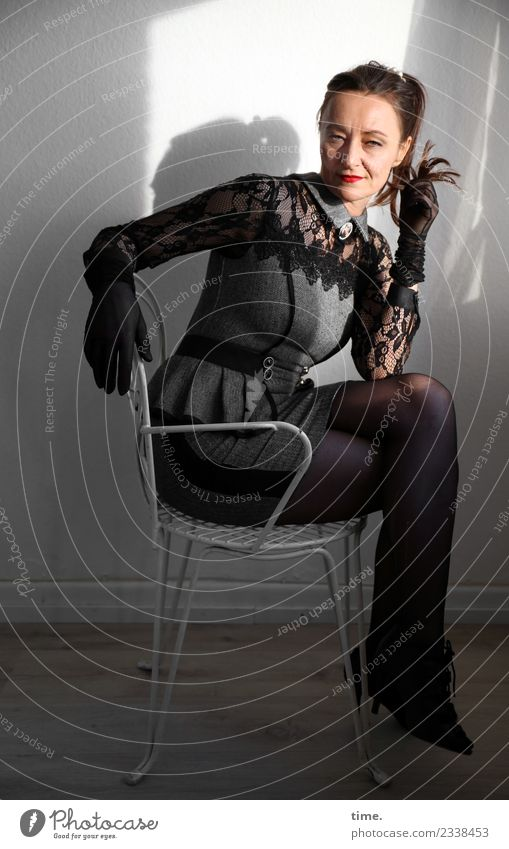 Mia Stuhl Raum feminin Frau Erwachsene 1 Mensch Mode Kleid Handschuhe brünett langhaarig Zopf beobachten Denken drehen Blick sitzen warten dunkel schön