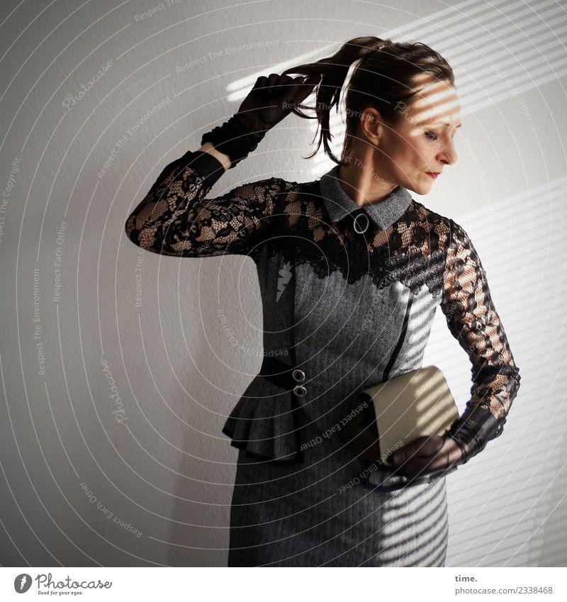 Mia feminin Frau Erwachsene 1 Mensch Kleid Handschuhe Handtasche brünett langhaarig Zopf beobachten festhalten Blick stehen außergewöhnlich dunkel elegant schön