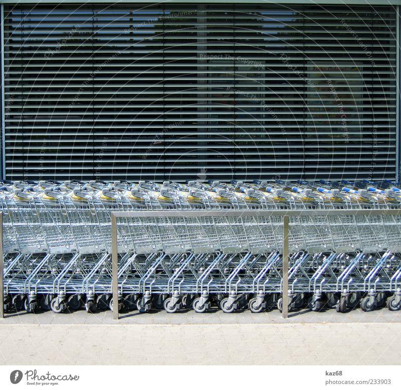 shopping Fenster Glas Metall Stahl grau silber Ordnung Dienstleistungsgewerbe Reichtum Zusammenhalt viele Einkaufswagen Einkaufsmarkt rollen Rad Rollladen
