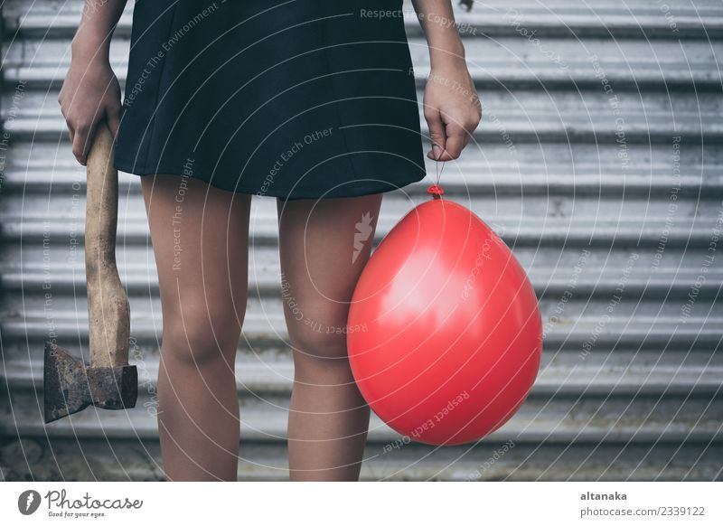 Teenagermädchen steht an einer Wand mit Ballon und Axt Lifestyle Körper Mensch Frau Erwachsene Jugendliche Hand Park Mode Luftballon Traurigkeit warten rot