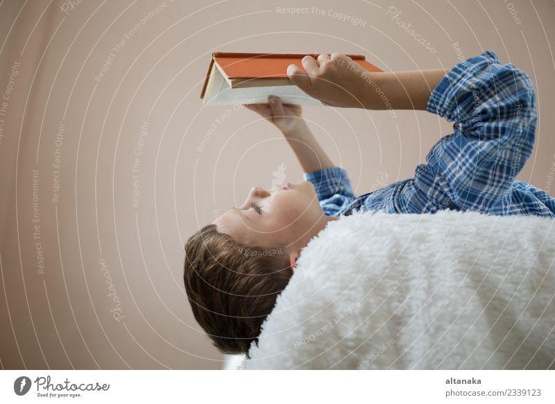 der kleine Junge liegt auf dem Bett und liest ein Buch. Lifestyle Freude Glück schön Gesicht Freizeit & Hobby lesen Kind Schule Mensch Mann Erwachsene