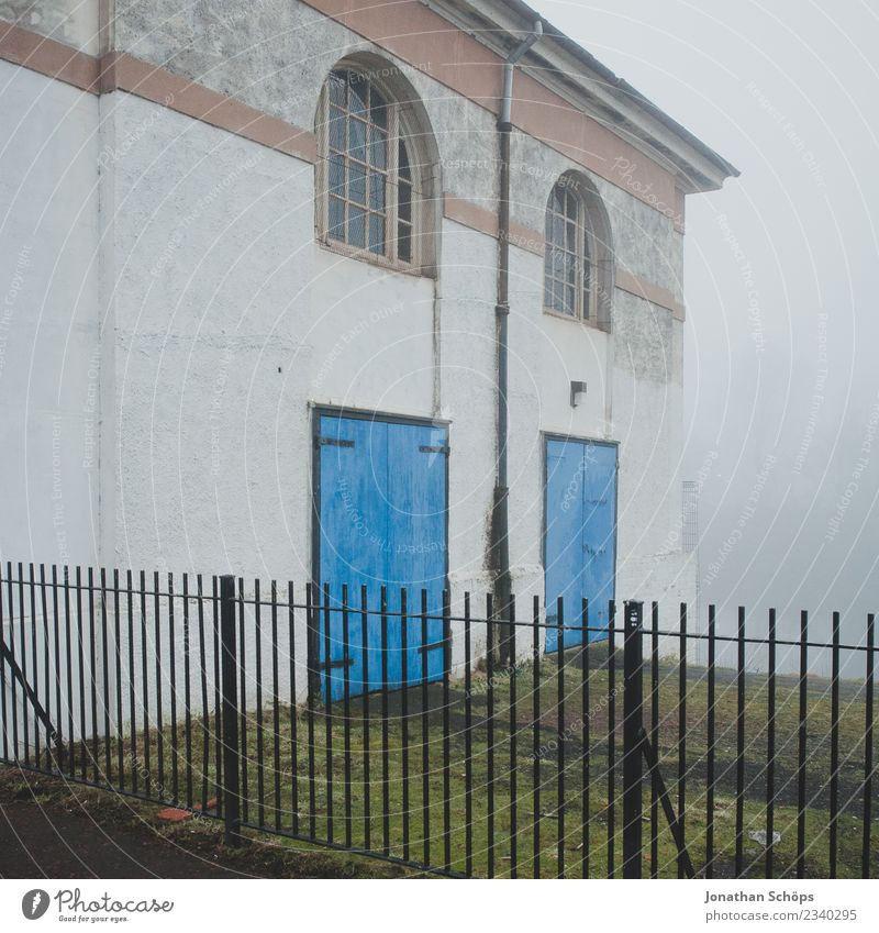 Haus im Nebel in Glasgow Stadt ästhetisch Nebelschleier Dunst Schottland Zaun Tür blau Fassade gruselig Nebelstimmung Nebellandschaft Farbfoto Außenaufnahme