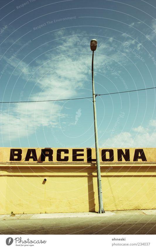 Immer eine Reise wert Himmel blau Wand Mauer Fassade Schriftzeichen Kabel Schönes Wetter Laterne Spanien Barcelona Blauer Himmel Stadtrand Oberleitung Wattewölkchen