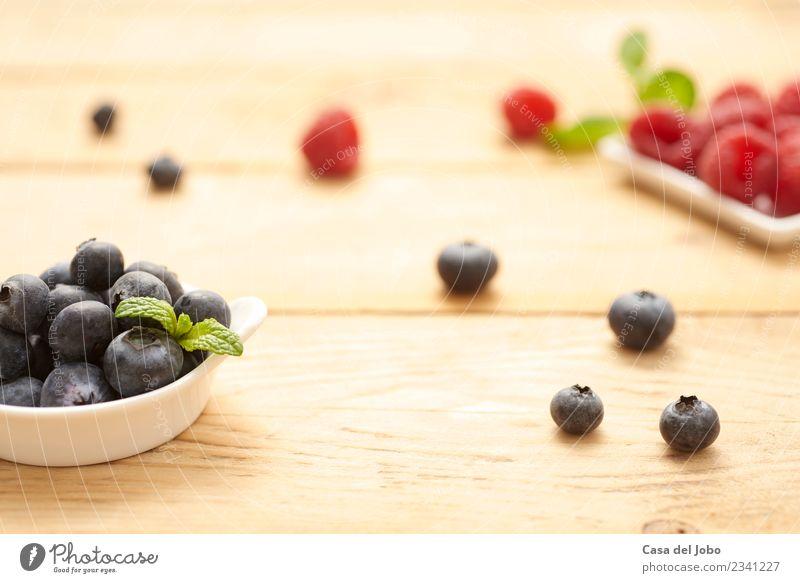 frische und rohe Heidelbeeren und Himbeeren auf Holzgrund Lebensmittel Frucht Dessert Ernährung Essen Frühstück Vegetarische Ernährung Diät Teller