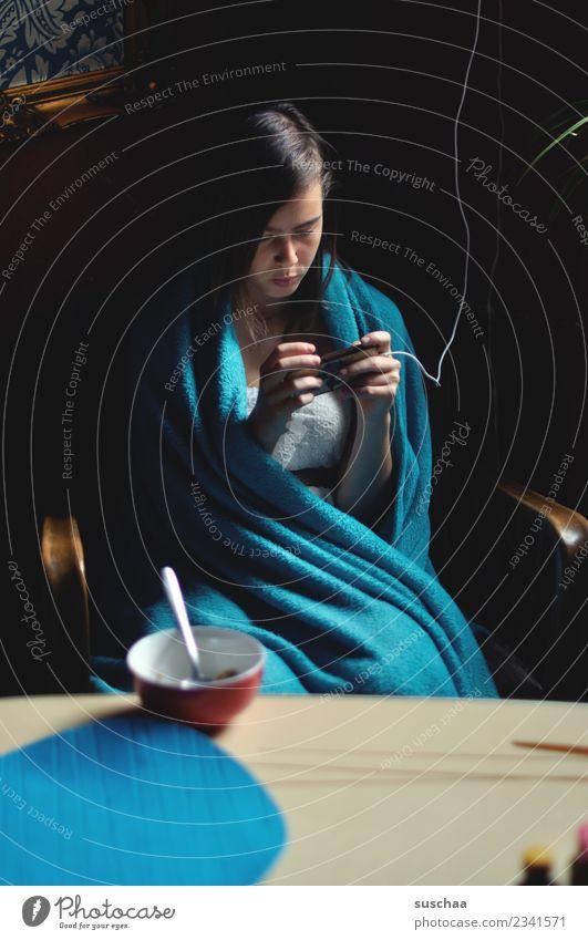 jugendliche sitzt in eine decke gehüllt am frühstückstisch und guckt in ihr smartphone Mädchen Kind Jugendliche Junge Frau 13-18 Jahre Internet Telefon SMS