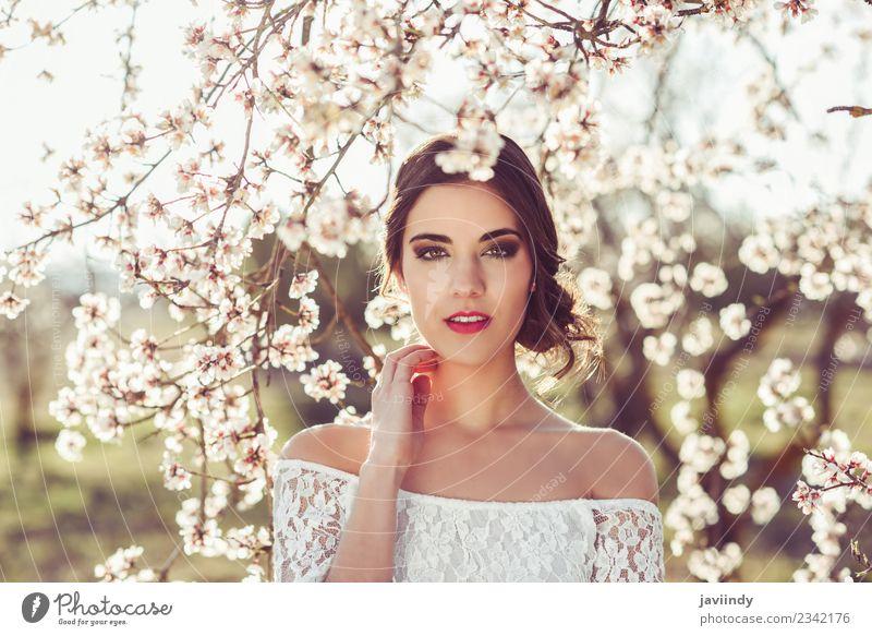 Junge Frau zwischen den Mandeln blüht im Frühling. Stil schön Mensch feminin Jugendliche Erwachsene 1 18-30 Jahre Natur Baum Blume Mode Kleid brünett weiß