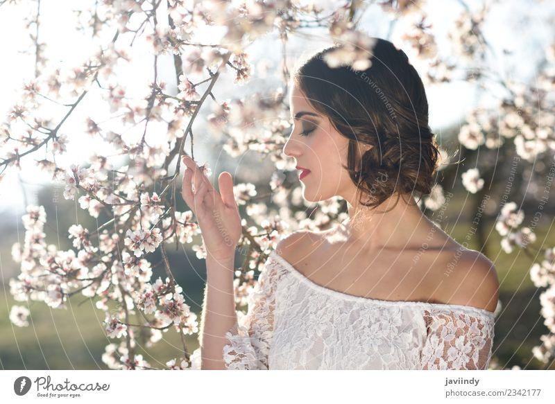 Junge Frau zwischen den Mandeln blüht im Frühling. Stil schön Gesicht Mensch feminin Jugendliche Erwachsene 1 18-30 Jahre Natur Baum Blume Blüte Park Mode Kleid