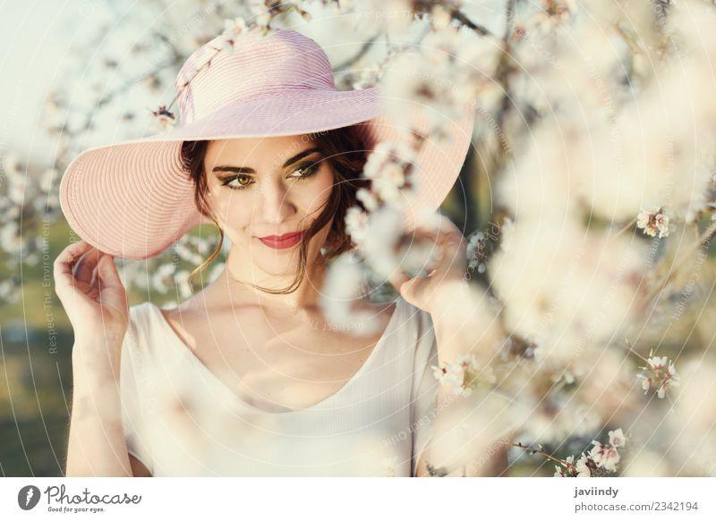 Junge Frau zwischen den Mandeln blüht im Frühling. Stil schön Gesicht Mensch feminin Jugendliche Erwachsene 1 18-30 Jahre Blume Mode Kleid Hut brünett rosa weiß