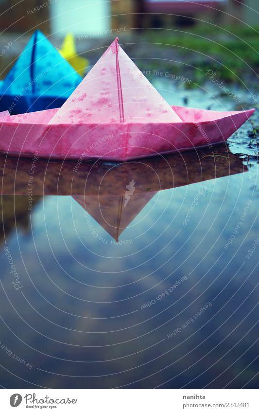 Bunte Papierboote im Wasser Umwelt Natur Wassertropfen Herbst Winter Klima Wetter schlechtes Wetter Regen Spielzeug Papierschiff Pfütze authentisch einfach
