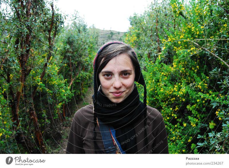 Cil im Peruanischen Dickicht Natur Blatt feminin lachen Blüte Sträucher Junge Frau Freundlichkeit Blühend Mütze brünett Schal Sympathie Hecke Zweige u. Äste