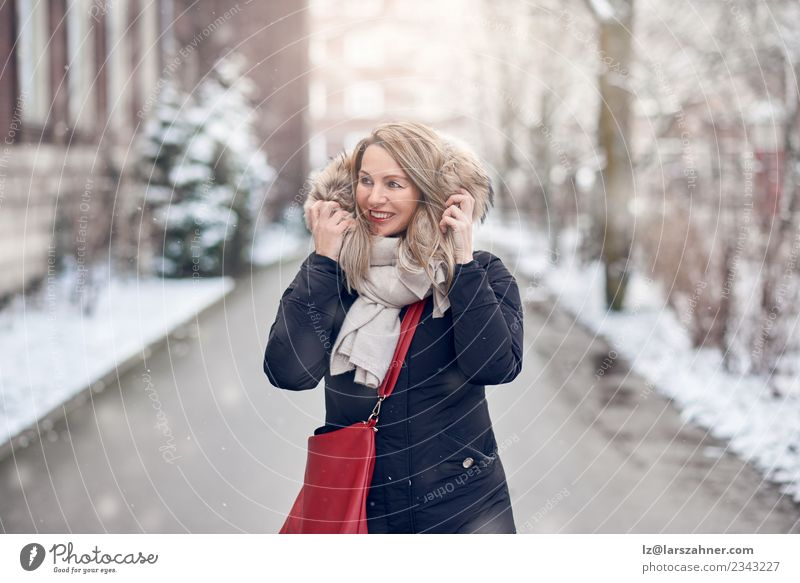 Lächelnde junge Frau, die auf einer verschneiten Straße geht. Glück schön Winter Schnee Erwachsene 1 Mensch 45-60 Jahre Natur Wetter Mode Jacke Mantel