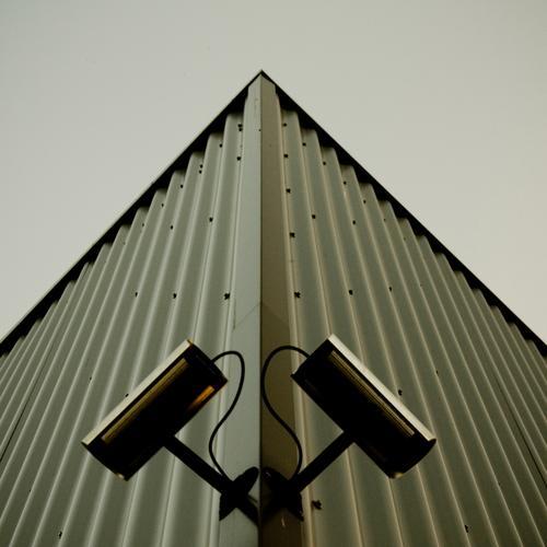 SYMMETRISCHE ÜBERWACHUNG Videokamera Haus Industrieanlage Fabrik Bauwerk Gebäude Architektur Fassade dunkel eckig Überwachung Container Wellblech Symmetrie grau