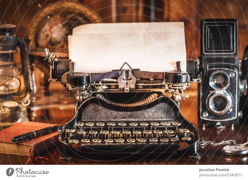 Vintage-Fotografiestilleben mit Schreibmaschine, Faltkamera, Weltkarte und Buch auf einem Holztisch. weiß gealtert Antiquität Hintergrund schwarz braun Business