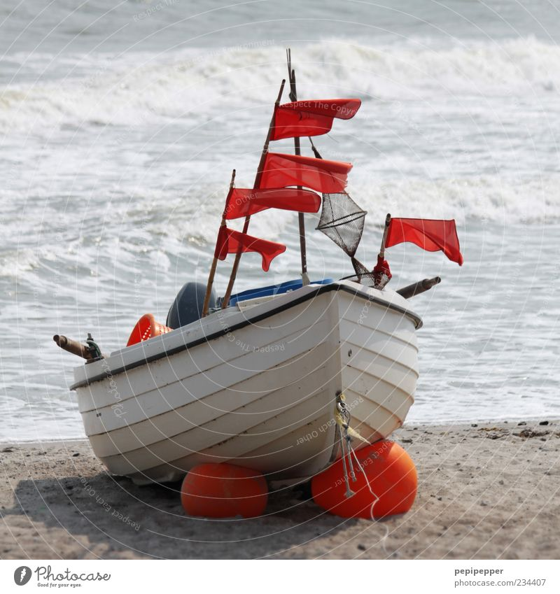 flagg-schiff Sommer Strand Meer Wellen Seil Motor Urelemente Sand Wasser Wind Küste Fischerboot Motorboot Holz Rost liegen warten Farbfoto Außenaufnahme Tag