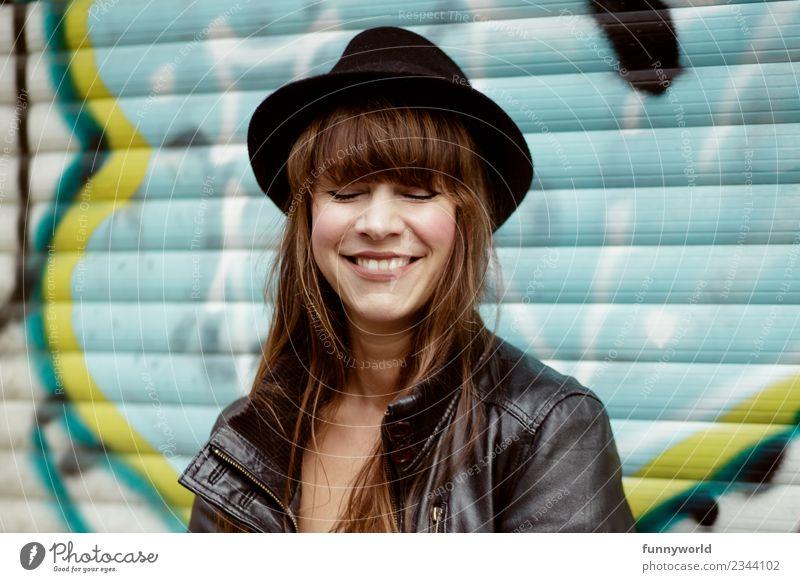 Frau mit Hut vor Graffiti lacht mit geschlossenen Augen Mensch feminin Erwachsene 1 30-45 Jahre Lächeln lachen Glück Fröhlichkeit Zufriedenheit selbstbewußt