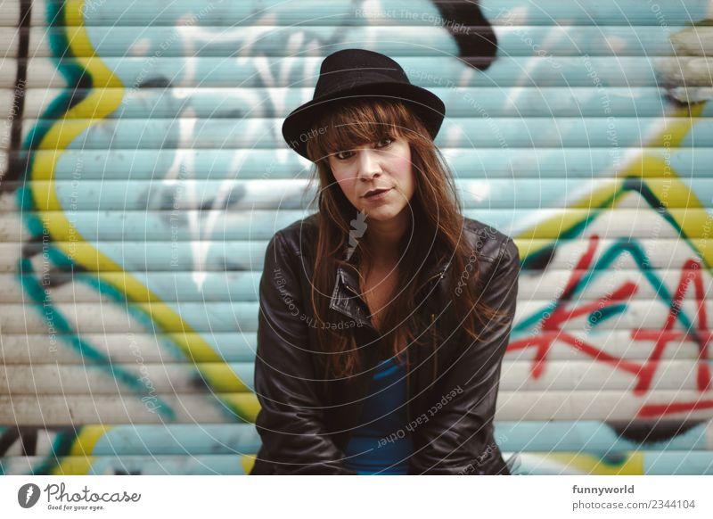 Coole Frau sitzt vor Graffiti und schaut in Kamera. Mensch Stadt schwarz Erwachsene feminin Stil Kraft sitzen Coolness Mut Hut selbstbewußt brünett direkt