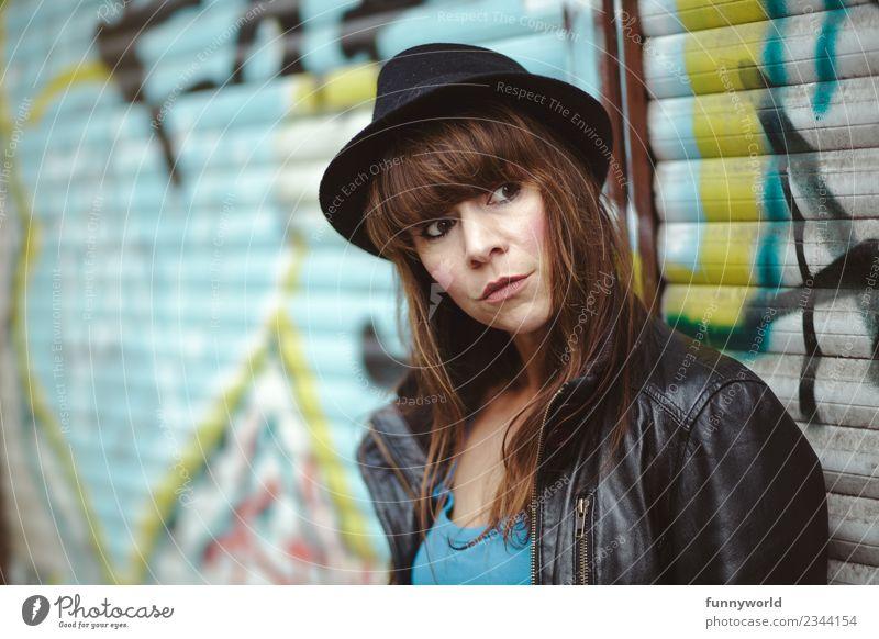 Frau steht vor Graffiti und schaut ernst zur Seite Mensch feminin Erwachsene 1 30-45 Jahre Coolness Stadt Hut Pony brünett skeptisch beobachten trendy einzeln