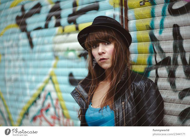 Coole Frau sitzt vor Graffiti und schaut in Kamera. Mensch Stadt schwarz Erwachsene feminin Stil Kraft Coolness Hut selbstbewußt Fragen Willensstärke ernst