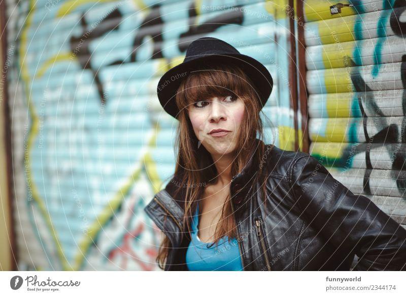 Frau mit Hut vor Graffiti schaut skeptisch zur Seite Mensch feminin Erwachsene 1 30-45 Jahre Blick stehen Denken warten beobachten Lederjacke schwarz Pony