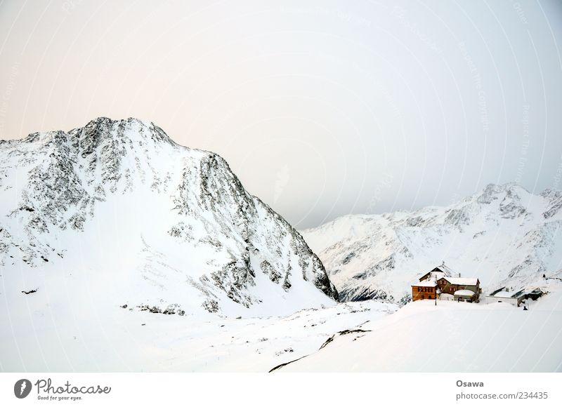 Haus in den Bergen Berge u. Gebirge Felsen Gipfel Schneebedeckte Gipfel Bergkamm Alpen Winter weiß kalt Himmel Dämmerung Hütte Schutzhütte Monochrom karg Ziel