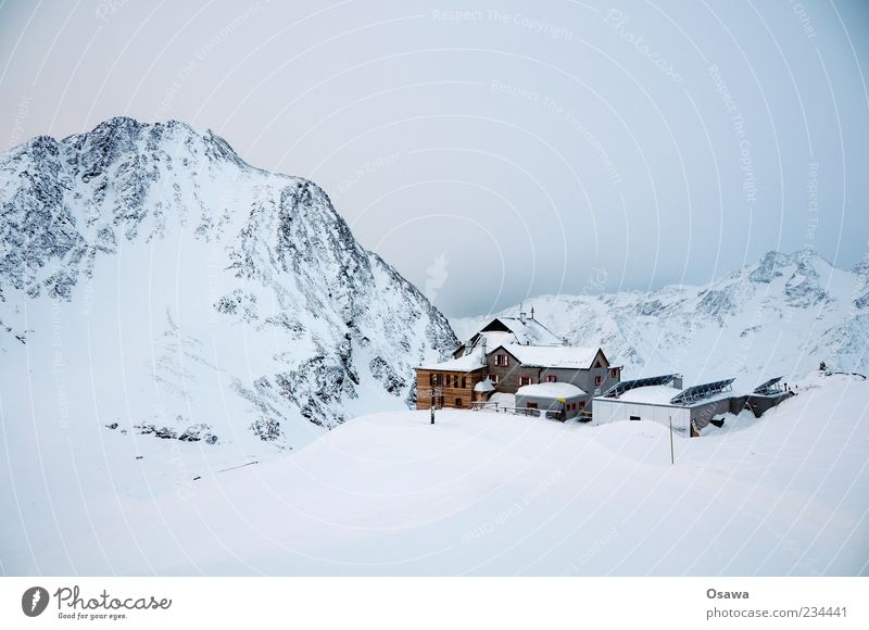 Haus in den Bergen Berge u. Gebirge Felsen Gipfel Schneebedeckte Gipfel Bergkamm Alpen Winter weiß kalt Himmel Dämmerung Hütte Monochrom karg Bergsteigen Ziel