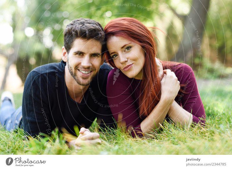 Schönes junges Paar, das auf Gras in einem Stadtpark liegt. Lifestyle Freude Glück schön Sommer Mensch Junge Frau Jugendliche Junger Mann Erwachsene 2