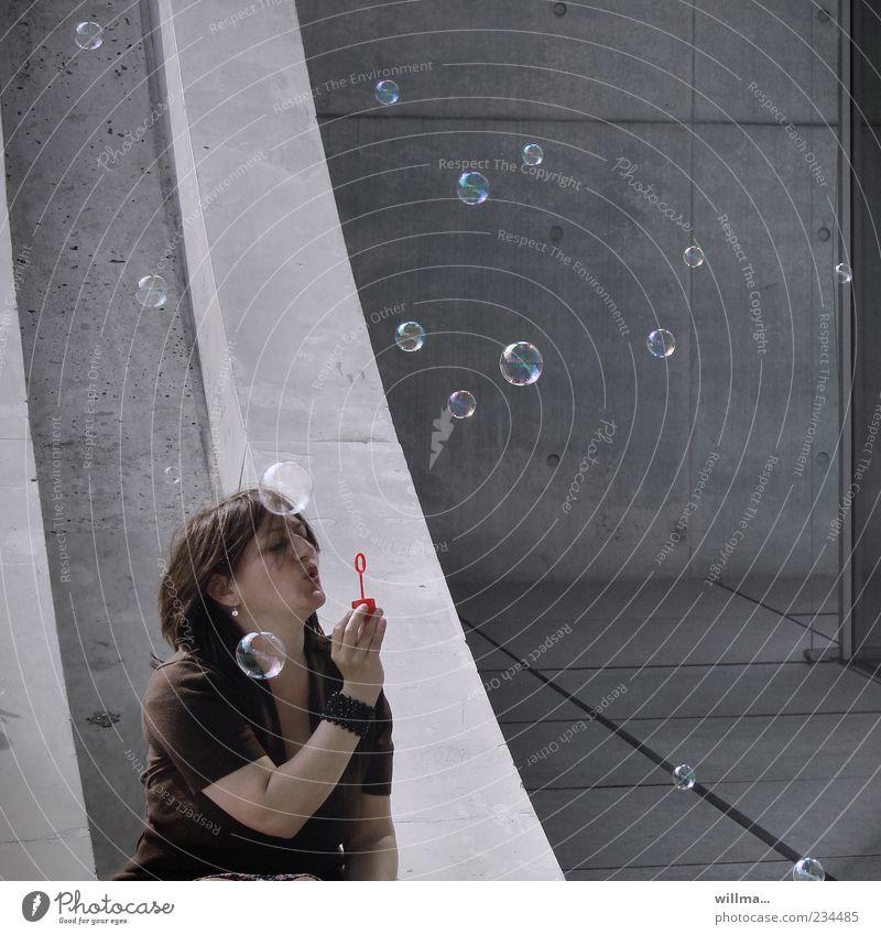 Frau sitzt vor Betonfasssade und machtS eifenblasen Seifenblase Erwachsene 1 Mensch 30-45 Jahre 45-60 Jahre Mauer Wand Lebensfreude Leichtigkeit Freude