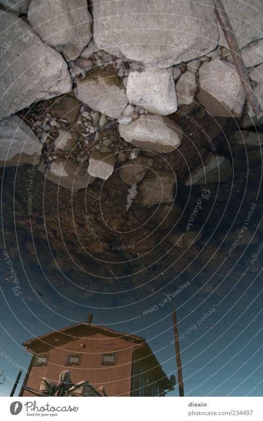 stony skies over paradise pt.2 blau Wasser Haus kalt grau Stein braun Felsen Boden Hafen Seeufer Flüssigkeit Hütte trashig Surrealismus Wasseroberfläche