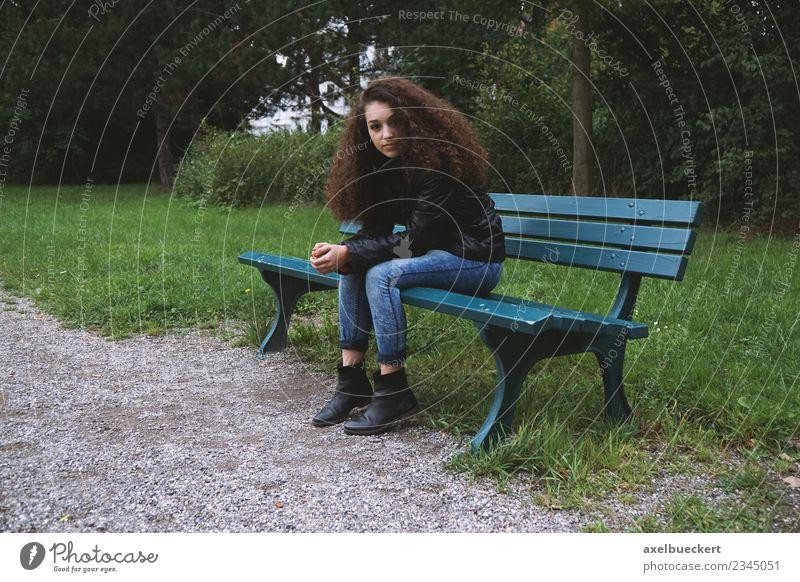 Junge Frau sitzt auf Parkbank Mensch feminin Jugendliche Erwachsene 1 13-18 Jahre Garten Jeanshose Jacke brünett langhaarig Locken sitzen Bank dunkel Einsamkeit