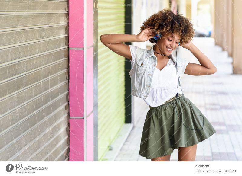 Schwarze Frau, die die Musik über Kopfhörer hört. Lifestyle Freude Haare & Frisuren Mensch feminin Junge Frau Jugendliche Erwachsene 1 18-30 Jahre Straße Mode