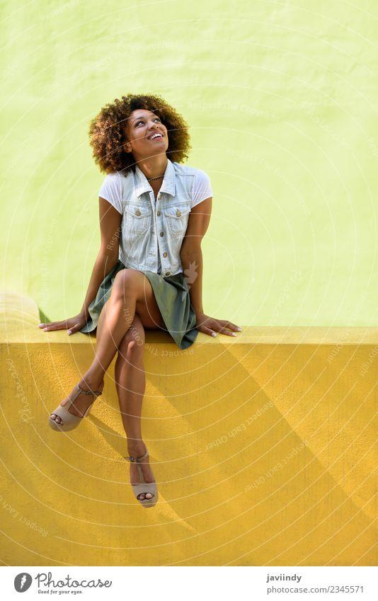 Schwarze Frau, Afro-Frisur, sitzt an einer Wand und lächelt. Lifestyle Stil Glück schön Haare & Frisuren Gesicht Mensch Junge Frau Jugendliche Erwachsene 1