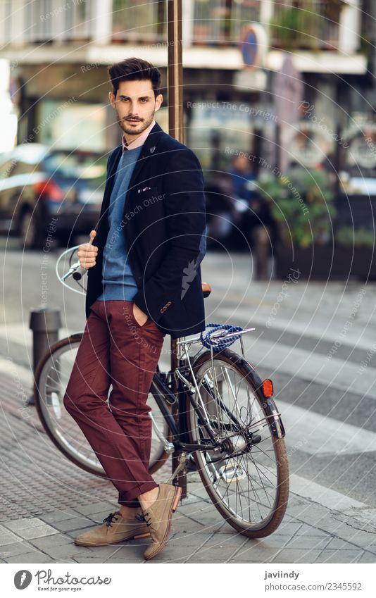 Mann auf der Straße im Anzug in der Nähe eines alten Fahrrads. Lifestyle elegant Stil schön Haare & Frisuren Business Mensch maskulin Junger Mann Jugendliche
