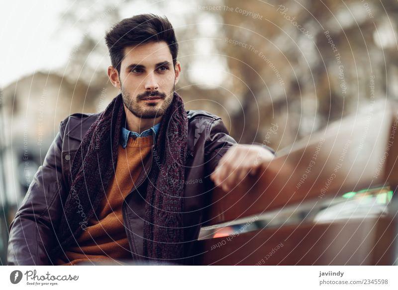 Nachdenklicher junger Mann, der auf einer städtischen Bank sitzt. Lifestyle Stil schön Haare & Frisuren Mensch Erwachsene Mode Jeanshose Pullover Jacke Leder