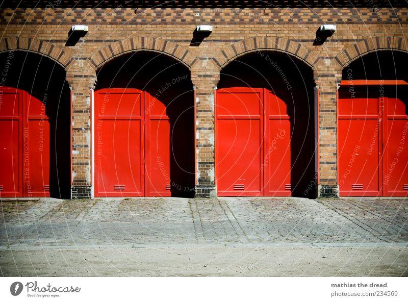TATÜ TATA Menschenleer Haus Bauwerk Architektur Mauer Wand Fassade Tür rot Feuerwehr Tor Symmetrie Backstein Muster schön Bürgersteig ruhig Lampe Wasser löschen