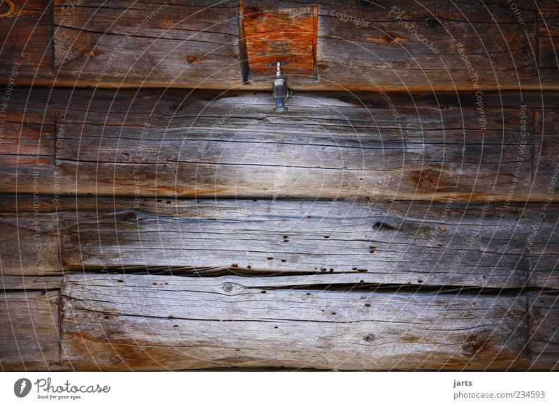 holzhaus mit wasseranschluss Haus Hütte alt ruhig Wasserhahn Holzwand Farbfoto Außenaufnahme Detailaufnahme Menschenleer Textfreiraum links Textfreiraum rechts
